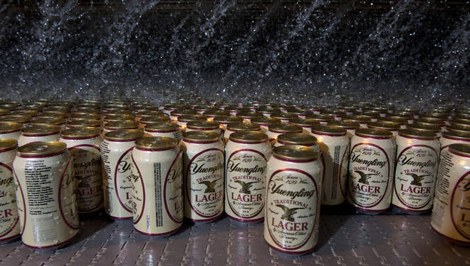 Water pours on cans of Yuengling Lager as they exit the pasteurizer at D.G.Yuengling & Son, Inc., America's oldest brewery. located in Pottsville, Pa., on Nov. 11, 2013.