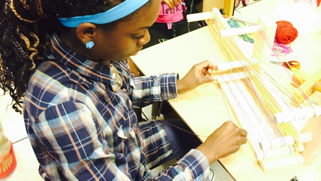 A student at the Quality Life Center in Dunbar works on a weaving project.
