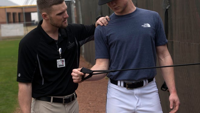 Kevin Knapp, Certified Athletic Trainer, with the Andrews Institute, left, helps Tate High School baseball player, Justin Barrett, with his arm stretching exercises before practice Friday, Feb. 9, 2018.