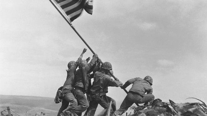 This Feb. 23, 1945, file photo shows U.S. Marines of the 28th Regiment, 5th Division, raising the American flag atop Mt. Suribachi in Iwo Jima, Japan.