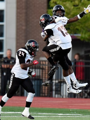 Pearl-Cohn cornerback Devin Hyde (13) celebrates with free safety Nickson Pierre, top, after Hyde returned a fumble for a touchdown against MBA during the first half Friday, Aug. 25, 2017.