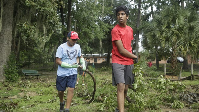 Akashi Bhat (left) and Varun Kambham (right) work to clear  tree limbs in a community clean up effort for Lafayette Park.