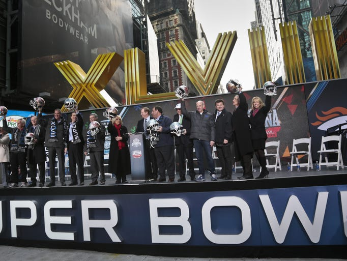 Officials from New York, New Jerse and Arizona raise souvenir football helmets Feb. 1, 2014, during a ceremony to pass official hosting duties of next year's Super Bowl to representatives from Arizona. The event was in New York's Super Bowl Boulevard.