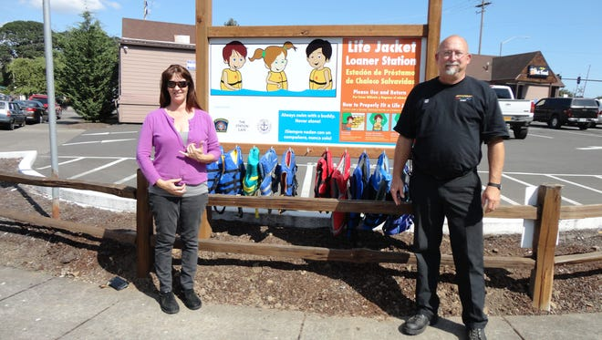 Michelle Nunes owner of Jefferson Statino Cafe, left,  and Jefferson Fire District Chief Jon Zeilman flank the new life-jacket station near the city's boat ramp.