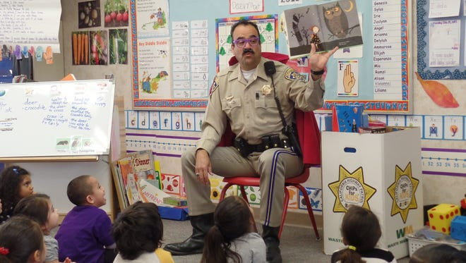 A California Highway Patrol officer reads to preschoolers.