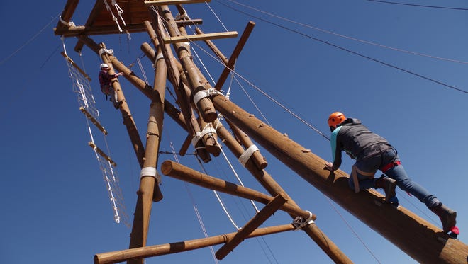 Shaneyka Yazzie climbs a pole in an undated photo provided San Juan College at its ropes course in Farmington.
