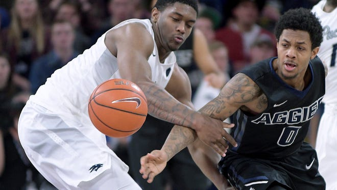 Utah State guard Shane Rector, right, and Nevada forward Cameron Oliver scramble for a loose ball during their game Wednesday.