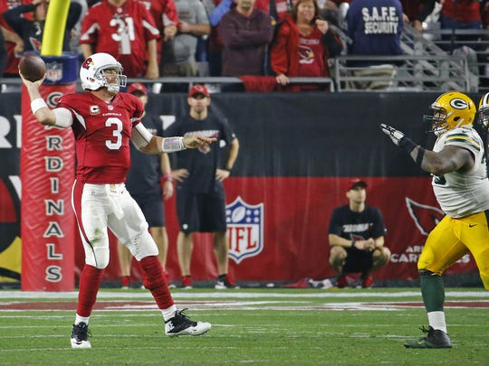 Carson Palmer escapes from a blitz to throw to wide receiver Larry Fitzgerald in overtime of the Cardinals' divisional playoff win over the Packers in 2016.