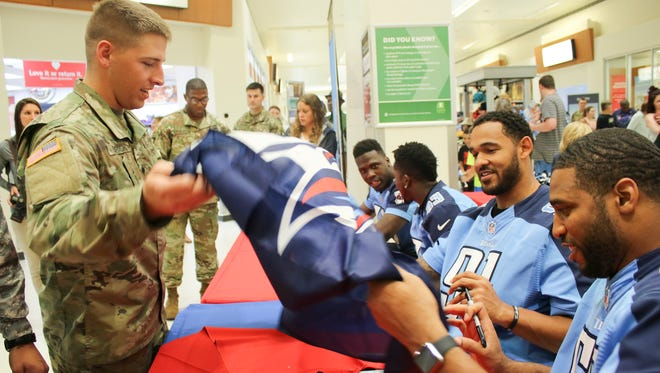Spc. Caleb Ehrich has his Titans flag signed by members of the team during the Titans meet and greet Monday at Fort Campbell.