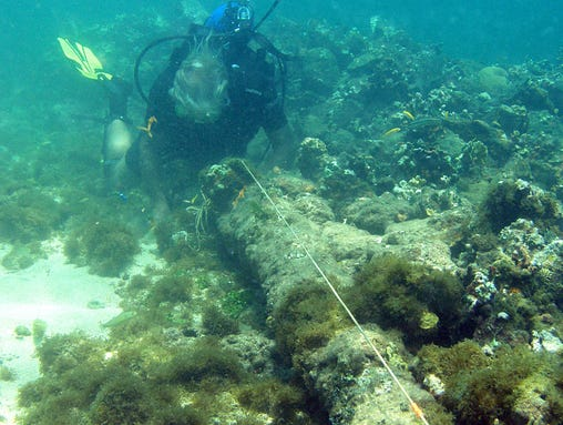 In this May 2003 photo, a diver measures a lombard cannon adjacent to a ballast pile, off the North coast of Haiti, at a site explorer Barry Clifford says could be the wreckage of Cristpher Colombus' flagship vessel the Santa Maria. Clifford said evidence that the wreck is the Santa Maria, which struck a reef and foundered on Christmas Day in 1492, includes ballast stones that appear to have come from Spain or Portugal and what looks like a 15th century cannon that was at the site during an initial inspection but has since disappeared. (AP Photo/Brandon Clifford)