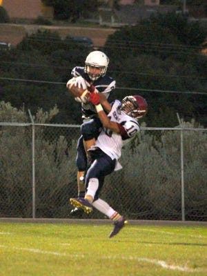 Silver's Steven Cross jumps and fights off a Deming cornerback on his 26-yard touchdown pass play that tied the game at 16-all with 11 seconds to play in the second quarter.