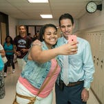 Junior Bre'a Dickerson, 17, stops to grab a selfie in the hall with Jeffersontown High School Principal Dr. Marty Pollio as classes end on the last day in seesion for Jefferson County Public Schools. June 5, 2015