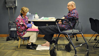 Stearns County public health nurse Gail Tinglov talks with Allen Gray as he gets his toenails trimmed during a Senior Health Clinic at the Stearns County Service Center in Waite Park in October 2014. Stearns County is considering eliminating the clinics.