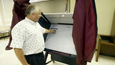 Lafayette Parish Clerk of Court Louis Perret, in a 2006 file photo, shows off a new voting machine. A bill to allow legislative oversight in selecting new voting machines advanced through the Senate and Governmental Affairs Committee