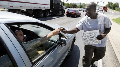 This photo from Aug. 21, 2016, shows Albert Perkins getting a few dollars from a passerby while panhandling at the corner of Memorial Boulevard and Broad Street.