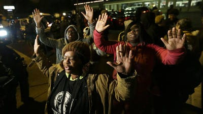 Barbara Jones and other protesters raise their hands Monday in Ferguson, Mo.