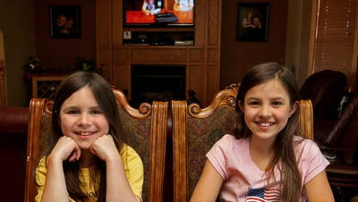 Natalie Gibson, 8, left, and her sister Meredith Gibson, 10, right, at their Johnston home on Tuesday, April 15, 2014. In front of them is their practice handgun, a Walther .22, that their father recently learned is illegal for them to fire because they're not 14 or older. Their father, Nathan Gibson, has been taking his two daughters to shooting ranges since they were 5, but this past weekend he and Natalie were told to leave. On the TV behind them is a Youtube video they posted about the situation.