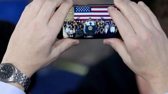 Audience member captures President Obama on his cell phone  during a speech in Ann Arbor, Michigan on raising the minimum wage