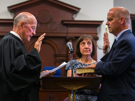 Retired District Judge Kenneth Neill swears in District Judge John A. Kutzman as his wife and fellow attorney, Jean Faure, holds the Bible at the Cascade County Courthouse on July 13.
