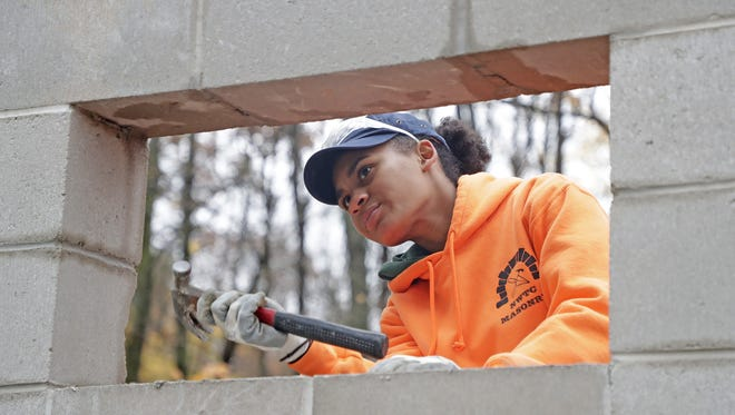 Jye Jude, a masonry student at Northeast Wisconsin Technical College, works on a building project behind the Norbert Hill Center in Oneida.