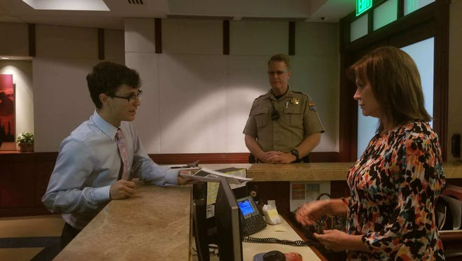 Jordan Harb hands a copy of students' gun control and student safety proposals to a secretary for Gov. Doug Ducey, while a Department of Public Safety trooper looks on.