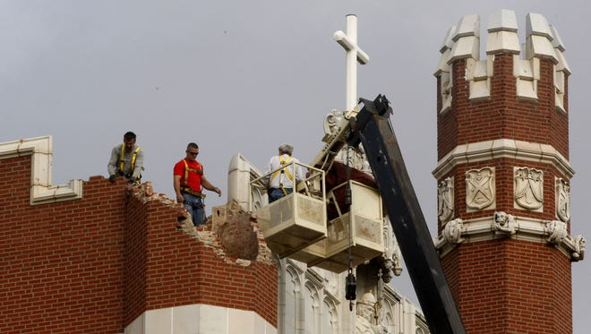 Maintenance workers inspect the damage to one of the spires on Benedictine Hall at St. Gregory's University following a magnitude-5.0 earthquake in Shawnee, Okla., in this file photo. A government report released Thursday, April 23, 2015 found that a dozen areas in the United States have been shaken in recent years by small earthquakes triggered by oil and gas drilling,  The man-made quakes jolted once stable regions in eight states, including parts of Alabama, Arkansas, Colorado, Kansas, New Mexico, Ohio, Oklahoma and Texas, according to researchers at the U.S. Geological Survey.  (AP Photo/Sue Ogrocki, File)