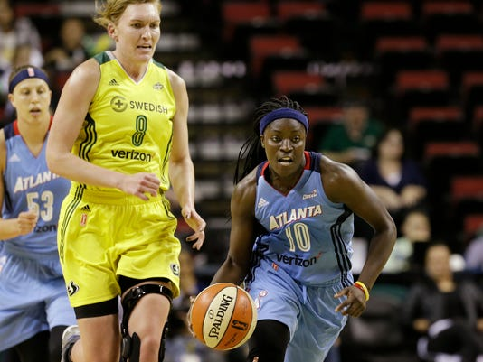 Atlanta Dream's Matee Ajavon (10) races ahead of Seattle Storm's Carolyn Swords (8) and Dream's Jordan Hooper during the first half of a WNBA basketball game Tuesday, June 13, 2017, in Seattle. (AP Photo/Elaine Thompson)