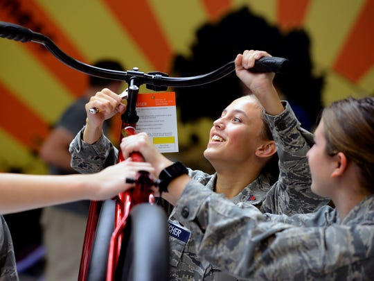 Simone Fletcher with Pensacola's Civil Air Patrol Cadet Squadron helps put together bikes Dec. 2, 2017, during onbike Pensacola's annual bike build at C.A. Weis Elementary School.