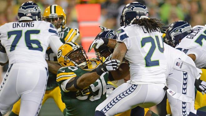 Green Bay Packers defensive lineman B.J. Raji (90) tackles Marshawn Lynch (24) against the Seattle Seahawks at Lambeau Field.