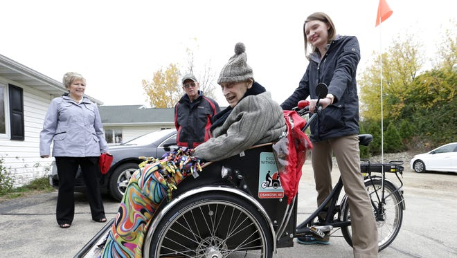 Ken Esslinger, 98, smiles after getting a rickshaw ride from Heather Paalman, an intern with Lutheran Homes of Oshkosh, at Alten Haus in the Town of Menasha. In back is Bonnie Behnke, director of development at Lutheran Homes, and Mike Matulle of Oshkosh, the nephew of Esslinger.