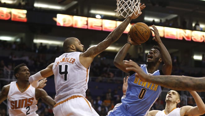 Suns' Tyson Chandler (4) contests a shot from Nuggets' Emmanuel Mudiay (0) at Talking Stick Resort Arena on November 27, 2016 in Phoenix, Ariz.