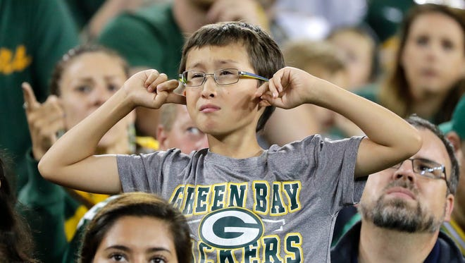 A Green Bay Packers fan covers his ears at Packers family night on Saturday, August 5, 2017, at Lambeau Field in Green Bay, Wis.