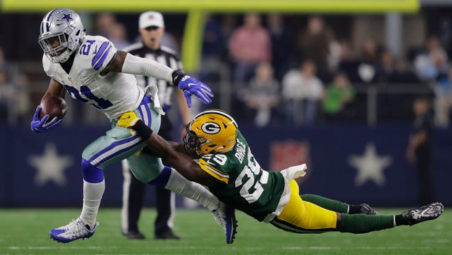 Dallas Cowboys running back Ezekiel Elliott fends off Green Bay Packers safety Kentrell Brice in the second quarter during their NFC divisional playoff game Jan. 15 in Arlington, Texas.