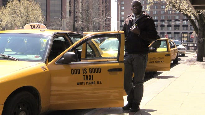 Jean-Lois Nicholas, a driver for God is Good Taxi of White Plains, picks up fares at the White Plains train station Thursday.