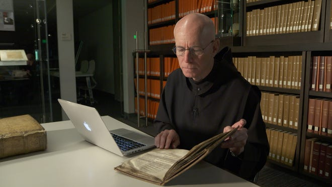 """The Rev. Columba Stewart studies a manuscript for a story on""""60 Minutes."""" Stewart, a Benedictine monk from St. John's Abbey, preserves historical manuscripts by digitizing them."""