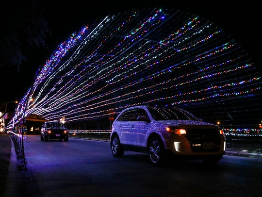 Cars drive through a tunnel of lights at the Concho