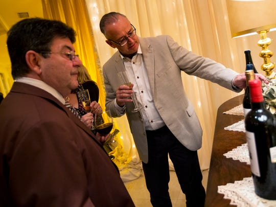 "Henri Jean, right, of Tampa, inspects the featured bottles of wine during the cocktail hour of the ""Sun, Moon and Stars"" vintner dinner hosted by Usha & Monte Ahuja with Joan & Bob Clifford in Naples, Florida on Friday, Jan. 27, 2017. This intimate, exclusive dining experience was illuminated by the expertise of two renowned vintners and the culinary talents of Wolfgang Puck."