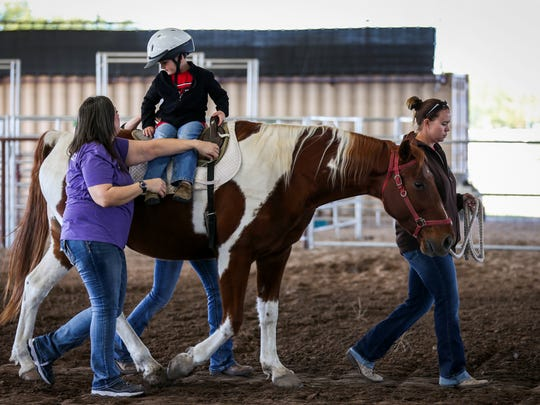 Sutton Biggs turns in the saddle during the around-the-world activity during therapeutic riding class Nov. 1, 2017, at Sonrisas Trails.