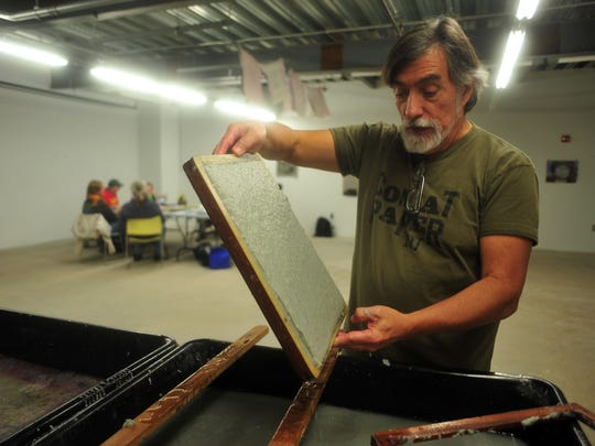 Vietnam veteran Walt Nygard drains water from a mold and deckle to make sheets of paper from uniforms. A writing workshop takes place in the background. Nygard leads Combat Paper NJ, a mobile workshop for veterans in Morristown through Oct. 31, that helps veterans tell their stories and heal their psyches.