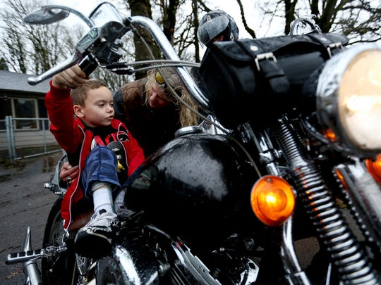 Jared Christensen, 8, the son of a resident at Her Place, a transitional home in Salem, sits on a motorcycle while talking with Colleen Crook, the organizer of the sixth annual Salem Bikers Gone Wild Toy Run, during a toy delivery at the home on Saturday, Dec. 12, 2015.