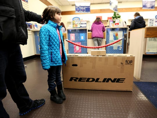 Jaydin Roth, 6, waits with her dad, Erik Roth, 40, of Salem, to mail packages at the main branch of the United States Post Office in Salem on Monday, Dec. 14, 2015.