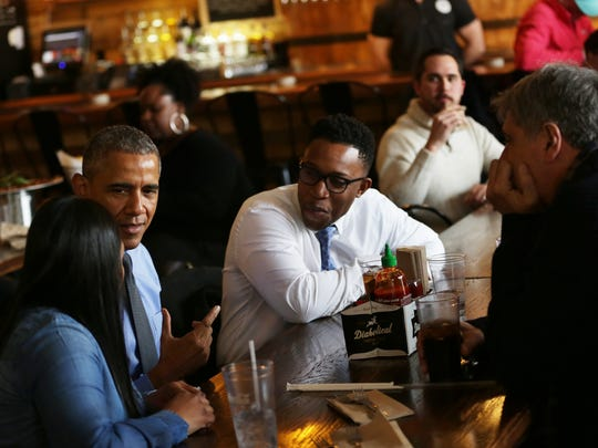 President Barack Obama has lunch with Teana Dowdell from UAW Local 22, left, emergency doctor Dr. Tolupe Sonuyi, center,  the founder of Shinola Tom Kartsotis, right and Detroit Mayor Mike Duggan at Jolly Pumpkin in Detroit.