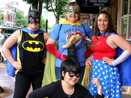 A legion of superheroes touting the upcoming Superhero Dash included Liz Henderson (Batman), Cindy Leinassar (Captain Awesome), Mitzi Smith (Wonder Woman) and Lisa Daniels, kneeling, (Bat Mite).