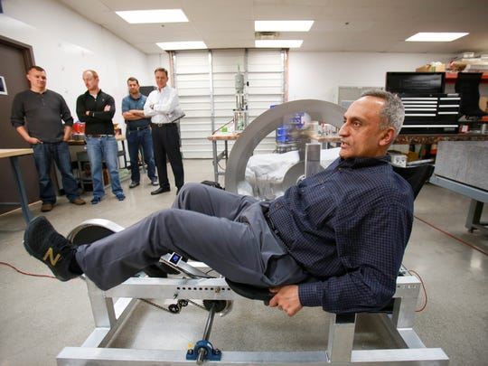 """Manoj Bhargava, CEO of Renew Enhanced Circulation, demonstrates how the """"free electric bicycle"""" generates and stores electricity at the lab in Farmington Hills in October 2015."""