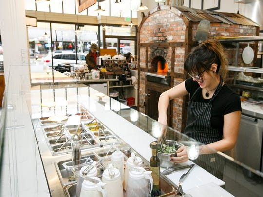 Chachi Medica mixes up a salad at Ritter's Housemade Foods in November of 2016. The restaurant brines, pickles and roasts their own salad additions and pizza toppings in-house.