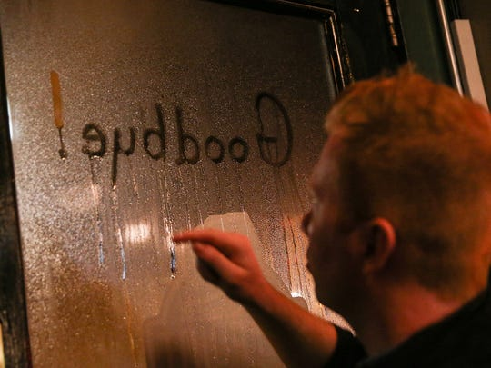 "Server Kyle Mock writes ""Goodbye!"" in the window condensation on the last night of business for Old Point Tavern on Mass Ave., Indianapolis, Thursday, Jan. 4, 2018. Chic and Patti Perrin, who have owned Old Point Tavern since 1990, are selling the bar to Cunningham Restaurant Group."