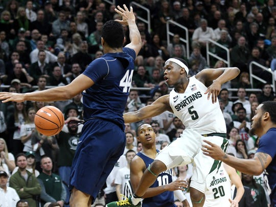 Michigan State's Cassius Winston, center, passes the
