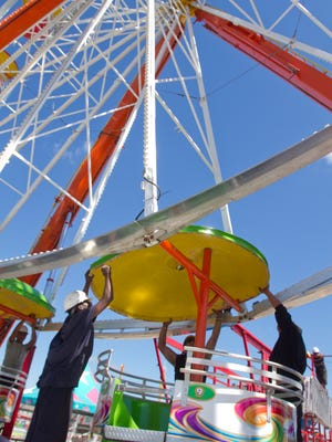Wade Shows carnival employees assemble the Sun Wheel Ferris wheel Wednesday, June 21, 2017 in preparation for the 33rd Michigan Challenge Balloonfest this weekend.
