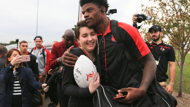 """Ballard High School student and cancer patient Amzie Smith received a hug as well as a football with a personal message """"Keep Fighting, Stay Strong"""" from Louisville quarterback Lamar Jackson before the Duke game Friday evening."""