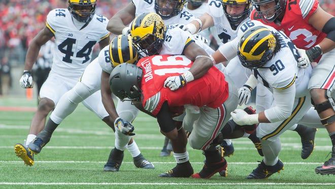 The Michigan defense gangs up on Ohio State quarterback J.T. Barrett.